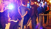 Police officers place one of two intoxicated young males into a cruiser outside of a popular pub in Halifax, Nova Scotia, April 20 , 2012. (Paul Darrow/The Globe and Mail)