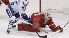 Vancouver Canucks right wing Derek Dorsett (15) tries shooting the puck past Detroit Red Wings goalie Jimmy Howard (35) during the third period of an NHL hockey game, Thursday, Nov. 10, 2016, in Detroit. (Carlos Osorio/AP)