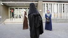 Nayet, centre, wearing a Burqa, and Kenza Drider, left, a French Muslim of North African descent, wearing a niqab, are seen after their release from a police station in Paris on April 11, 2011. That was the day France's ban on full face veils, a first in Europe, went into force. (GONZALO FUENTES/REUTERS)