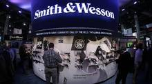 In this Tuesday, Jan. 14, 2014, file photo, trade show attendees examine handguns and rifles in the Smith & Wesson display boot at the Shooting Hunting and Outdoor Tradeshow, in Las Vegas. (Julie Jacobson/The Associated Press)