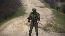An armed man, believed to be a Russian serviceman, stands guard outside an Ukrainian military base in the village of Perevalnoye, near the Crimean city of Simferopol, March 12, 2014. (THOMAS PETER/Reuters)