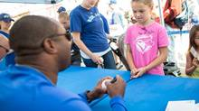 Madison Leslie of St. Mary's, Ont., has her baseball signed by Toronto Blue Jays alumni Devon White during the Baseball Family Street Festival, part of the Canadian Baseball Hall of Fame's induction weekend events in St. Mary's, Ont., on June. 21. (Geoff Robins/THE CANADIAN PRESS)