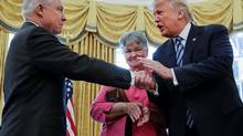 President Donald Trump shakes hands with Attorney General Jeff Sessions, accompanied by his wife Mary, after he was sworn-in by Vice President Mike Pence, Thursday, Feb. 9, 2017, in the Oval Office of the White House in Washington. (AP Photo/Pablo Martinez Monsivais)