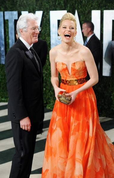 """Either Richard Gere is reenacting that famous scene from """"Pretty Woman"""" with Elizabeth Banks or he just asked how her she feels about sleeping with old men at the Vanity Fair Oscars party in West Hollywood on Sunday. (Evan Agostini/AP)"""