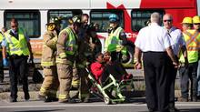 A female bus passenger is led away to a waiting ambulance. A Via Rail train collided with an Ottawa OC Transpo bus during this morning rush hour September 18, 2013 in Ottawa. (Dave Chan For The Globe and Mail)