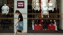 A pedestrian strolls in front of renewed Japanese apparel chain Uniqlo in a Ginza shopping district in Tokyo, in this file photo. (Junji Kurokawa/AP)