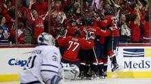 Justin Williams of the Washington Capitals is mobbed by teammates after scoring the game-winning goal in overtime to give the Capitals a 2-1 win over Toronto Maple Leafs in Game 5. (Rob Carr/Getty Images)
