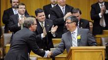 Saskatchewan Premier Brad Wall shakes hands with Finance Minister Ken Krawetz after he delivered the provincial budget at the Legislative Assembly of Saskatchewan in Regina on Wednesday, Mar. 19, 2014 (Michael Bell/The Canadian Press)