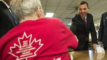 Ontario PC leader Tim Hudak, right, meets with members of the Royal Canadian Legion Branch 147 during a campaign stop in Barrie, Ont., on May 9. (Nathan Denette/The Canadian Press)