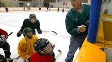 Former NHLer Brian Skrudland goes over drills with his peewee hockey team in Calgary in 2003. Hockey players, parents and leagues across the country are debating the pros and cons of bodychecking. (Jeff McIntosh/The Globe and Mail)