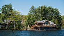 A large cottage stands on an island in this aerial photograph taken above Muskoka, Ont. The area is attracting American investors who want a rustic retreat that comes with 800-thread-count sheets. (James MacDonald/Bloomberg)