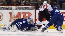 Toronto Maple Leafs goalie James Reimer (L) reaches for the puck as New Jersey Devils Ryan Carter (2nd R) tries to get his stick on it while being chased by Leafs Colton Orr in the first period of their NHL game in Toronto April 15, 2013. (FRED THORNHILL/REUTERS)