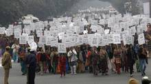 Women hold placards at a protest in India. (ADNAN ABIDI/REUTERS)