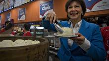 British Columbia Premier Christy Clark serves steamed buns to a customer while visiting a bakery in Vancouver on May 14. Like Prime Minister Stephen Harper in the 2011 federal campaign, Ms. Clark harped relentlessly on the theme of building a strong economy and preserving stable government handling of its finances. (ANDY CLARK/REUTERS)