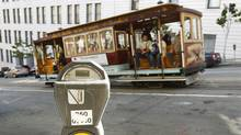 A cable car passes a parking meter near San Francisco's financial district. San Francisco City Attorney Dennis Herrera on Monday, June 23, 2014 issued a cease-and-desist demand to a mobile app called Monkey Parking, which allows people to auction off public parking spaces that they're using to other nearby drivers. (2009 file photo) (Ben Margot/AP Photo)