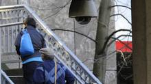 Pedestrians walk below a security camera located at Granville and Cordova streets in downtown Vancouver during the Vancouver Winter Olympics in February 2010. (Tim McKenna/The Globe and Mail)
