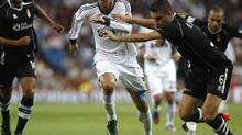 Real Madrid's Cristiano Ronaldo (L) challenges Granada's Guilherme Siqueira during their Spanish first division match at the Santiago Bernabeu stadium in Madrid September 2, 2012. (PAUL HANNA/REUTERS)
