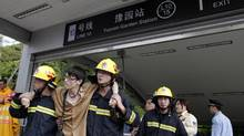Firemen help evacuate a victim outside the Yuyuan Garden station after a subway crash in Shanghai. (Carlos Barria/Reuters/Carlos Barria/Reuters)