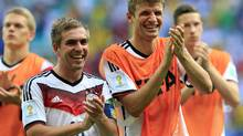 Germany's Philipp Lahm, left, and Thomas Mueller applaud after the group G World Cup soccer match between Germany and Portugal at the Arena Fonte Nova in Salvador, Brazil, Monday, June 16, 2014. Germany won the match 4-0. (Bernat Armangue/AP)