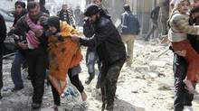A Free Syrian Army fighter helps a family after a jet missile hit the al-Myassar neighbourhood of Aleppo on Feb. 20, 2013. (MUZAFFAR SALMAN/REUTERS)