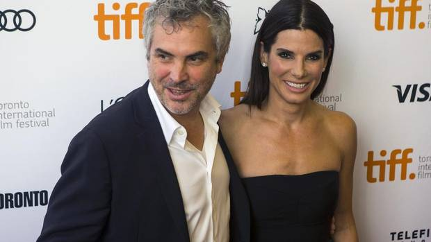 Alfonso Cuaron and Sandra Bullock pose for a photograph on the red carpet at the gala for the new movie Gravity during the 2013 Toronto International Film Festival, Sept. 8, 2013. (Chris Young/The Canadian Press)