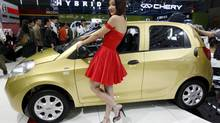 A model poses next to a Chery Riich M1 car at the Shanghai International Auto Show in this file photo. (NIR ELIAS/REUTERS)