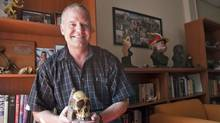 Paleoanthropologist Lee Berger, who with his 9-year-old son discovered a new hominid species, Australopithecus sediba, holds a replica of a cranium fossil in his office at the University of the Witwatersrand in Johannesburg. He uses Google Earth to seek fossil sites, and promotes his findings on Facebook and Twitter. (Erin Conway-Smith)