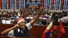 A trader wearing a Santa Claus hat celebrates during a last day of trading inside a Philippine Stock Exchange at the financial district of Makati city, metro Manila Dec. 27, 2013. (Romeo Ranoco/Reuters)