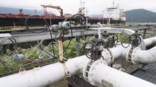 A ship receives its load of oil from the Kinder Morgan Trans Mountain Expansion Project's Westeridge loading dock in Burnaby, British Columbia, on June 4, 2015. (JONATHAN HAYWARD/THE CANADIAN PRESS)