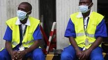 Workers wearing protective masks sit at the Felix Houphouet Boigny international airport in Abidjan August 12, 2014. Ivory Coast on Monday banned air travellers from Guinea, Liberia and Sierra Leone, the three countries worst-hit by the Ebola outbreak, and ordered its flagship carrier Air Cote d'Ivoire to cease flights to and from them. Ivory Coast has not registered any cases but is seen as vulnerable given its shared borders with Guinea and Liberia. (LUC GNAGO/REUTERS)