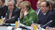 France's President Francois Hollande, right, delivers a speech to open an international summit on youth unemployment in the European Union as he sits next to German Chancellor Angela Merkel, centre, and Austrian Labor Minister Rudolf Hundstorfer, left, at the Elysee Palace in Paris Nov. 12, 2013. (Michel Euler/Reuters)