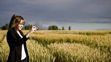 Smiling woman standing in field with digital camera (Jupiterimages/www.jupiterimages.com)