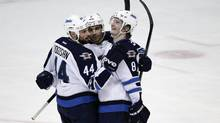 Winnipeg Jets' Evander Kane, center, celebrates his goal with Zach Bogosian, left, and Jacob Trouba during the second period of an NHL hockey game against the Anaheim Ducks, Tuesday, Jan. 21, 2014, in Anaheim, Calif. (Jae C. Hong/AP)