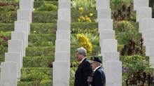 Prime Minister Stephen Harper, left, walks with a Second World War veteran at Sai Wan War Cemetery at a Remembrance Day ceremony in Hong Kong on Nov. 11, 2012. (BOBBY YIP/REUTERS)