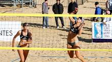 Sarah Pavan, left, looks on as teammate Heather Bansley smashes the ball in a match against Britta Buthe and Karla Borger of Germany in the FIVB Corrientes Grand Slam in Corrientes, Argentina, on May 24, 2013. (HO/THE CANADIAN PRESS)