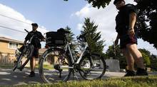 Police officers look on in the neighbourhood where Toronto police Constable James Forcillo lives in Toronto, August 19, 2013. (MARK BLINCH/REUTERS)