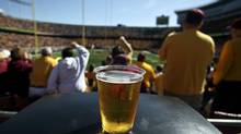 In this Sept. 8, 2012, photo, a beer sits atop a garbage can as Minnesota college football fans fans cheer a first quarter play against New Hampshire at TCF Bank Stadium in Minneapolis, Minn. (David Joles/AP Photo/The Star Tribune)