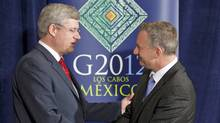 Prime Minister Stephen Harper shakes hands with International Trade Minister Ed Fast after a news conference at the G20 Summit in Los Cabos, Mexico, on June 19, 2012. (Adrian Wyld/The Canadian Press)