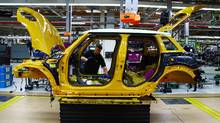 An employee installs a wiring loom into a Mini car as it travels along the assembly line at the BMW Mini car production plant in Oxford, west of London. (GEOFF CADDICK/AFP/Getty Images)