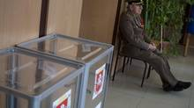 An election observer sits at a polling station in Simferopol, Ukraine, Sunday, March 16. (Ivan Sekretarev/AP)