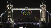 The Olympic rings are seen atop the iconic Tower Bridge over river Thames in London, coinciding with one month to go until the start of the London 2012 Games. (Lefteris Pitarakis/AP)