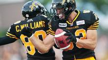 Andy Fantuz (right) and Chris Williams of the Hamilton Tiger-Cats celebrate Fantuz's touchdown in the first half of their game against the Toronto Argonauts in Canadian Football League action at Ivor Wynne Stadium in Hamilton, Ontario, Saturday, July 14, 2012. (Geoff Robins/THE CANADIAN PRESS)