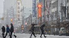 Pedestrians are seen crossing Granville Street in downtown Vancovuer, B.C., on Wednesday, December, 19, 2012. A heavy snowfall warning has been issued for the city. (Jonathan Hayward/The Canadian Press)