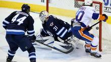 New York Islanders' Michael Grabner (40) scores a game winning goal on Winnipeg Jets goaltender Ondrej Pavelec (31) as Zach Bogosian (40) looks on, during overtime NHL action in Winnipeg, Tuesday, March 4, 2014. (Trevor Hagan/THE CANADIAN PRESS)