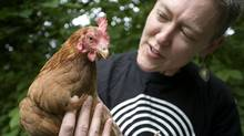 Lorraine Johnson, author of the new book City Farmer, and Nog, one of three chickens she has in her backyard in downtown Toronto. (Ashley Hutcheson for The Globe and Mail)