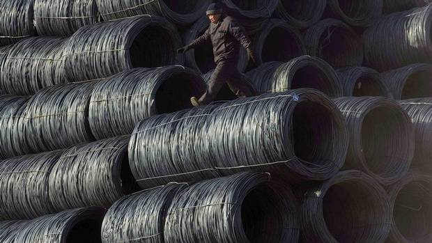 A labourer walks on coils of steel wire at a steel market in Shenyang, Liaoning province, China. Slowing construction and industrial activity has hit Chinese steel demand and prices hard in the past few weeks. (SHENG LI/REUTERS)