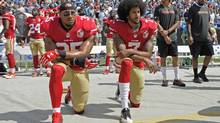 San Francisco 49ers safety Eric Reid, left, and quarterback Colin Kaepernick kneel during the national anthem before an NFL game against the Carolina Panthers in Charlotte on Sunday. (Mike McCarn/AP)