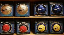 """Nike brand soccer balls bearing the """"Swoosh"""" logo on display at a Nike store. (RICHARD CLEMENT/RICHARD CLEMENT/REUTERS)"""