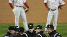 Umpires discuss a call at first base (Julie Jacobson/AP)