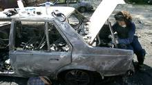 A criminology graduate student checks over a car that has been torched to track evidence at the Justice Institute of B.C. Aug 23, 2006. (Laura Leyshon/ The Globe and Mail/Laura Leyshon/ The Globe and Mail)